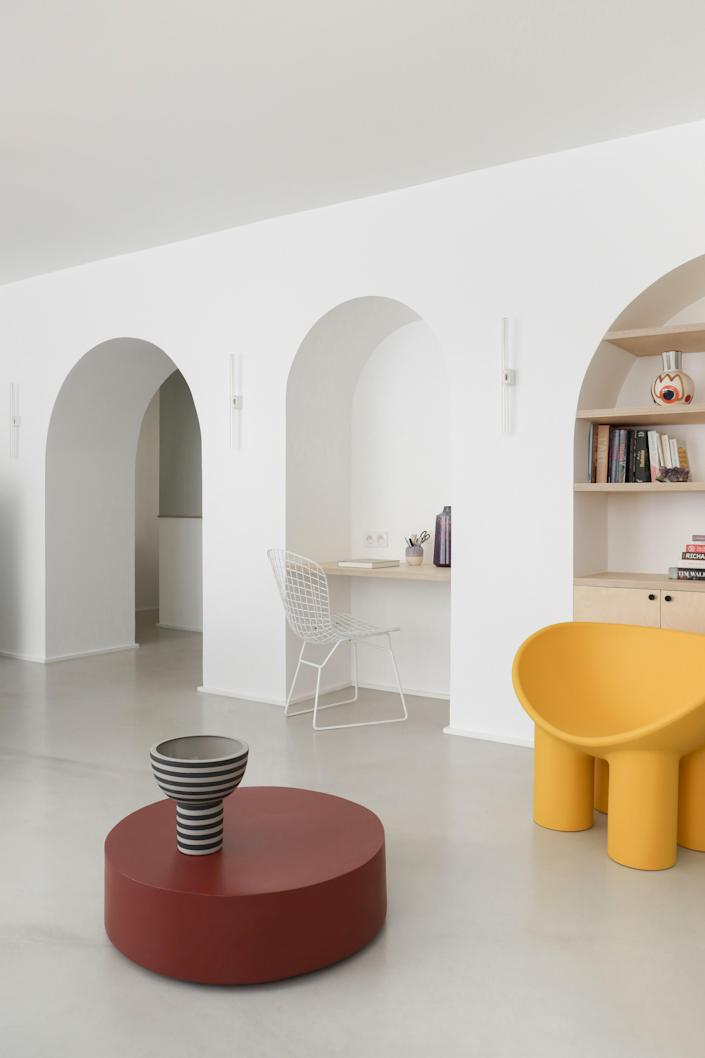 """AFTER: One of the biggest changes to the home was this arched """"living wall"""" created by the architects. The yellow Roly Poly chair by Faye Toogood adds a pop of color to the living room furnished with a Serax coffee table and vases by AYTM and LRNCE."""