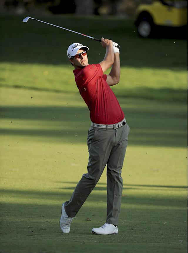 In this photo released by OneAsia, Adam Scott of Australia plays a shot during the first round of the Australian PGA Championship at the RACV Royal Pines Resort golf club on Australia's Gold Coast Thursday, Nov. 7, 2013. (AP Photo/OneAsia, Khalid Redza)