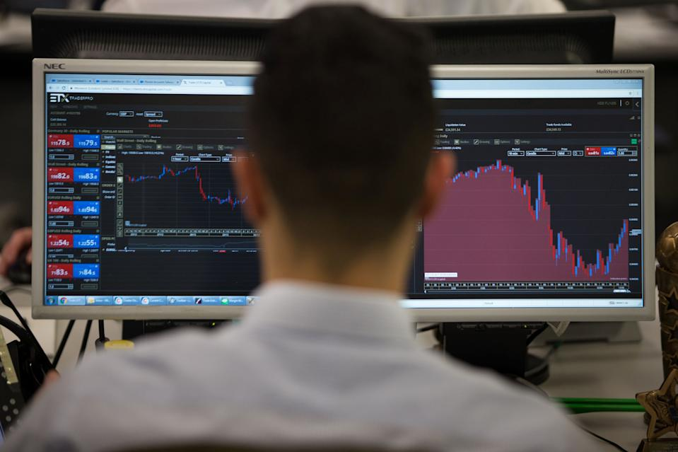 A trader studies information on trading screens at ETX Capital in central London. Photo: Daniel Leal-Olivas/AFP via Getty Images