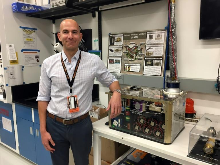 NASA scientist Charles Malespin poses next to a reproduction of the SAM instrument aboard the rover Curiosity on Mars