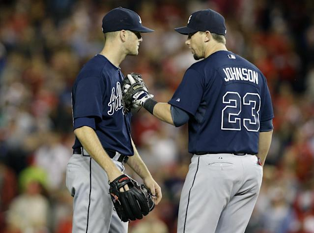 Atlanta Braves relief pitcher Alex Wood, left, is restrained by third baseman Chris Johnson (23) during the fifth inning of a baseball game against the Washington Nationals at Nationals Park, Wednesday, Sept. 18, 2013, in Washington. Home plate umpire CB Bucknor called a pitch a ball with the bases loaded and a full count. (AP Photo/Alex Brandon)
