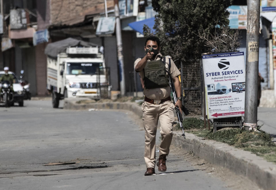 A policeman gestures towards the media near the site of a shootout at Sopore, 55 kilometers (34 miles) north of Srinagar, Indian controlled Kashmir, Saturday, June 12, 2021. Two civilians and two police officials were killed in an armed clash in Indian-controlled Kashmir on Saturday, police said, triggering anti-India protests who accused the police of targeting the civilians. (AP Photo/Mukhtar Khan)