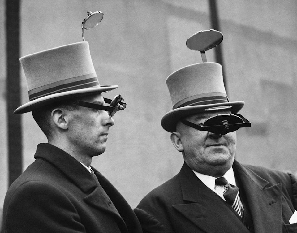 <p>Two British men in 1937 model the newest periscope hat, which allows them to get a better view from above. </p>