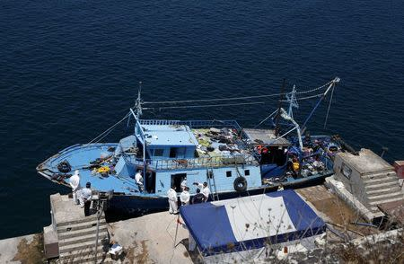 Hazmat and forensic officers work on board a fishing boat, on which 19 migrants are reported to have died, at the Armed Forces of Malta Maritime Squadron base in Valletta's Marsamxett Harbour, after it was towed to Malta by the AFM