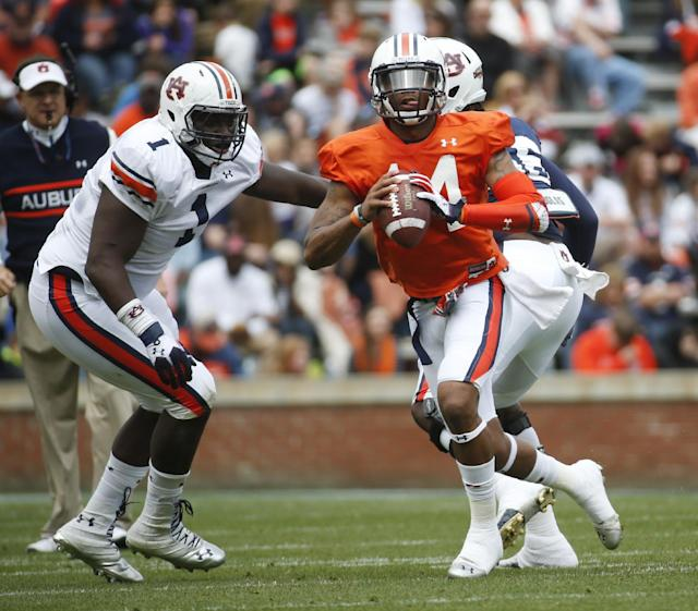 Auburn quarterback Nick Marshall (14) scrambles as defensive tackle Montravius Adams (1) watches during the first half of the A Day spring game for the NCAA college football team, Saturday, April 19, 2014 in Auburn, Ala. (AP Photo/John Bazemore)