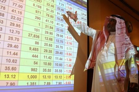 A saudi man inspect a screen showing stock prices at ANB Bank, in Riyadh