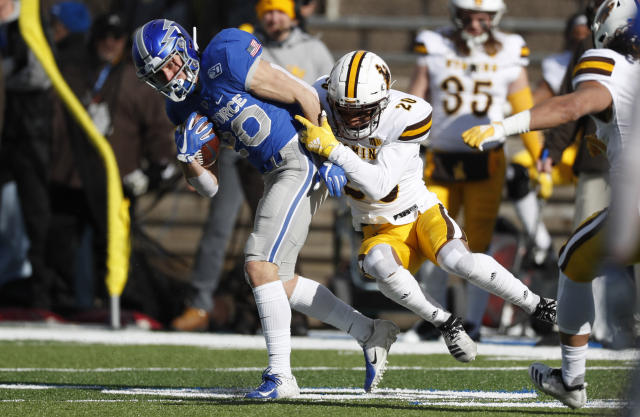 Air Force wide receiver Benjamin Waters, left, is tackled by Wyoming cornerback Azizi Hearn after pulling in a pass in the first half of an NCAA college football game Saturday, Nov. 30, 2019, at Air Force Academy, Colo. (AP Photo/David Zalubowski)