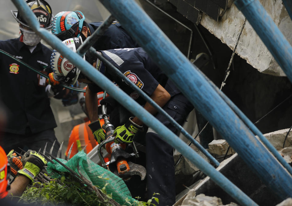 Rescue teams use rescue cutters as they search for possible victims trapped in a house that collapsed in Bangkok, Thailand, Saturday, April 3, 2021. A number of people were killed after a three-story house in Bangkok collapsed on Saturday due to fire, the city government said. (AP Photo/Str)