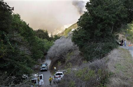 Police and fire vehicles sit at the entrance to a canyon during a wild fire in Big Sur, California, December 17, 2013. REUTERS/Michael Fiala