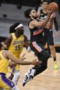 San Antonio Spurs' Derrick White (4) shoots as Los Angeles Lakers' Montrezl Harrell (15) and Talen Horton-Tucker defend during the first half of an NBA basketball game Friday, Jan. 1, 2021, in San Antonio. (AP Photo/Darren Abate)