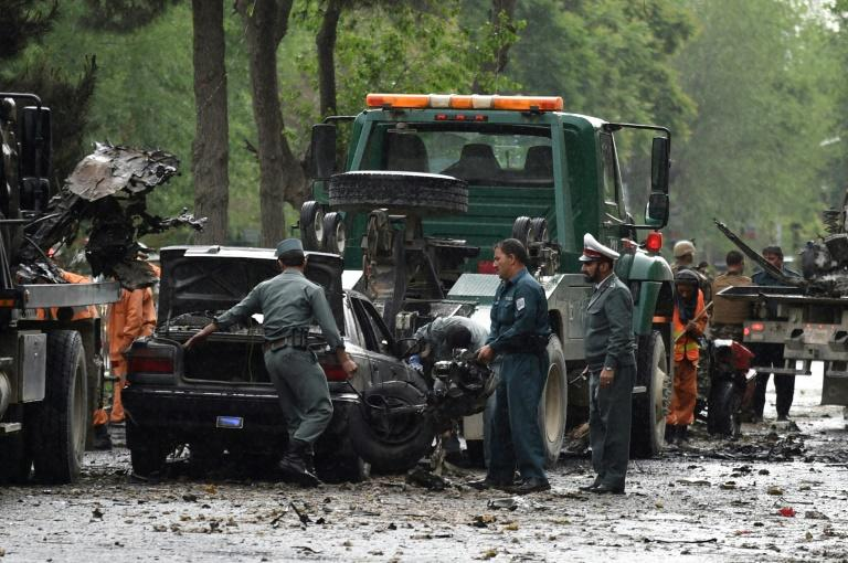 Afghan security personnel investigate the site of a suicide attack that targeted a foreign forces convoy near the US embassy in Kabul on May 3, 2017
