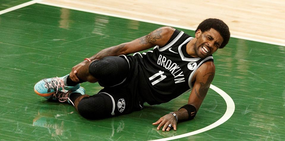 Nets guard Kyrie Irving (11) grabs his leg after being injured during the second quarter against the Milwaukee Bucks during game four in the second round of the 2021 NBA Playoffs. 20210613_neb_sh5_072.JPG