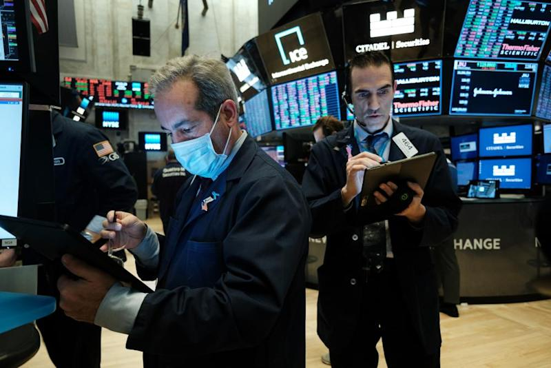 Traders, some in medical masks, work on the floor of the New York Stock Exchange last week. Traders are now trading remotely.