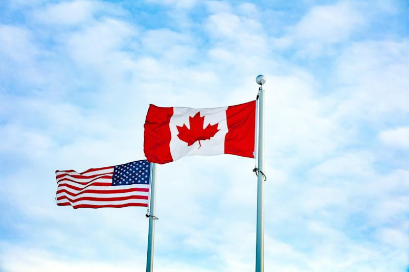 Canadian and American flag together, Canada flag forward in front