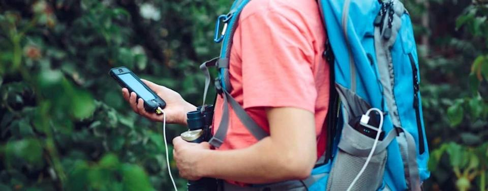 hiker holding charging phone