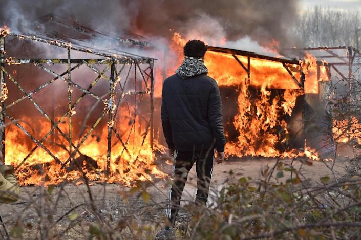 """A migrant looks at shacks burning during the dismantling of half of the """"Jungle"""" migrant camp in the French northern port city of Calais, on February 29, 2016 (AFP Photo/Philippe Huguen)"""