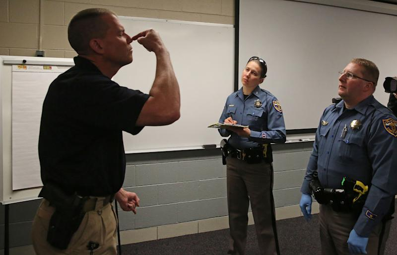 Simulating a roadside investigation of a potentially intoxicated driver, Colorado State Trooper Sgt. David Blatner, left, pretends to be high and struggling to touch his nose with his eyes closed as he trains troopers Carrie Jackson, center, and Toby Cox in a several week long Drug Recognition Expert class, at the Colorado State Patrol Training Academy, in Golden, Colo., Thursday March 6, 2014. The ongoing training is happening as Colorado struggles to keep accurate statewide records on marijuana-impaired drivers, with state police chiefs saying they need more money to train officers in recognizing stoned drivers. (AP Photo/Brennan Linsley)