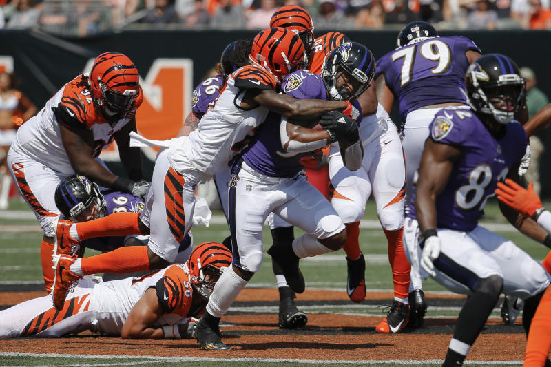 Baltimore Ravens running back Javorius Allen, center, fights for yards against the Bengals. (AP)