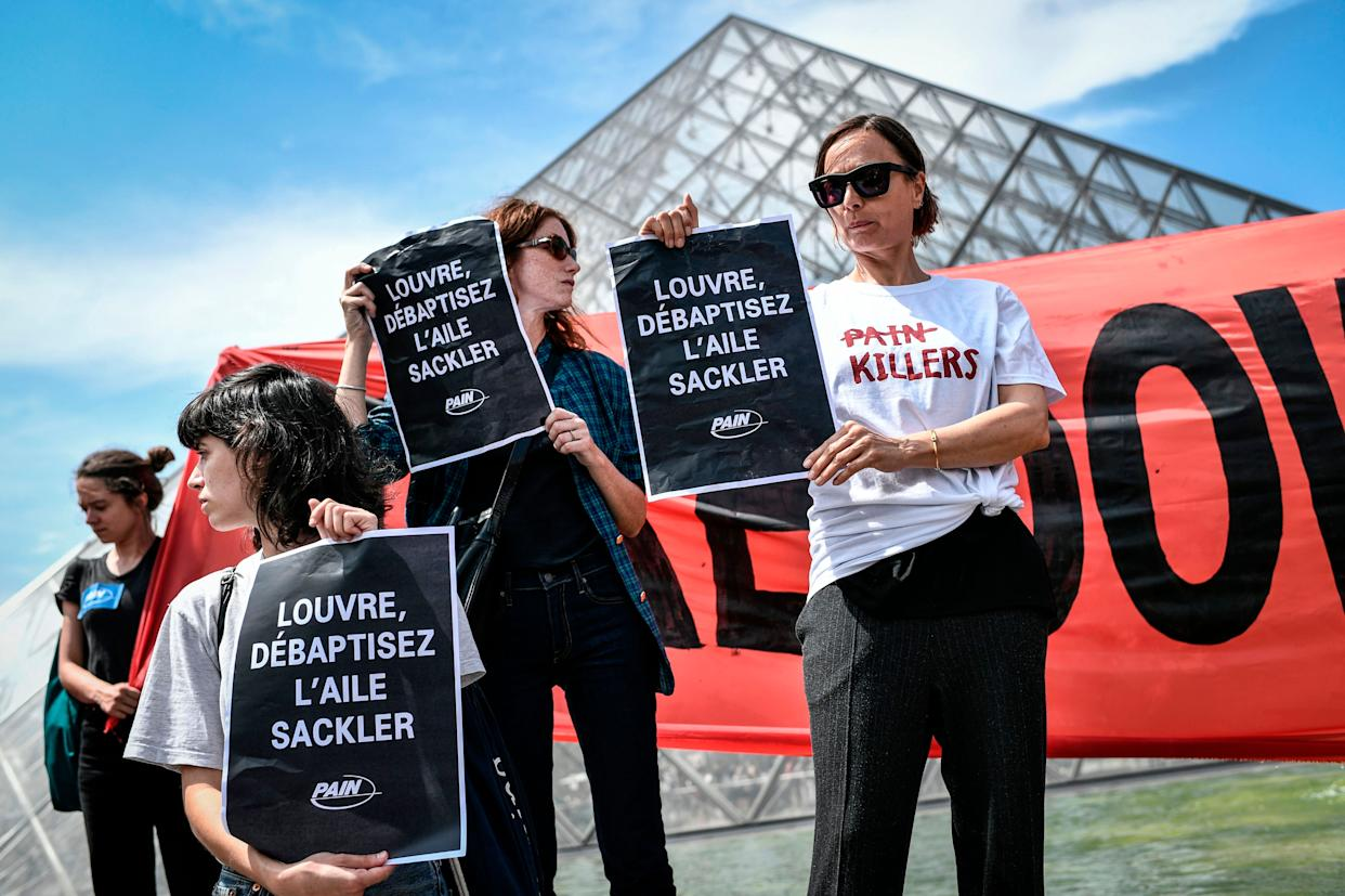 """Protesters hold banners reading """"Shame on Sackler"""" and """"Take down the Sackler name"""" in front of the Pyramid of the Louvre Museum on July 1 in Paris. (Photo: STEPHANE DE SAKUTIN via Getty Images)"""