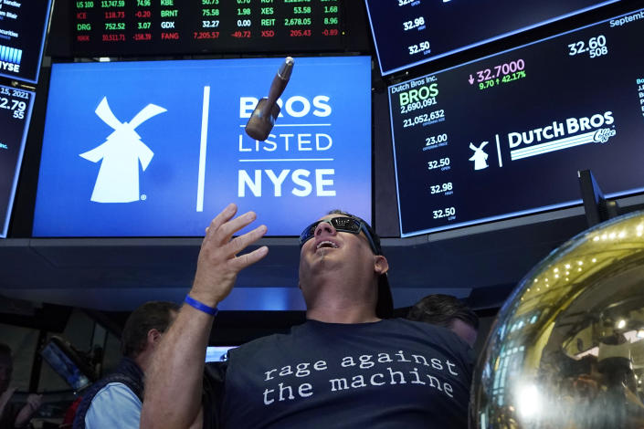 CORRECTS TITLE TO EXECUTIVE CHAIRMAN, NOT PRESIDENT - Dutch Bros Coffee Co-founder and Executive Chairman Travis Boersma tosses the gavel after he rang the ceremonial first trade bell on the floor of the New York Stock Exchange, as his company's IPO opens, Wednesday, Sept. 15, 2021. (AP Photo/Richard Drew)