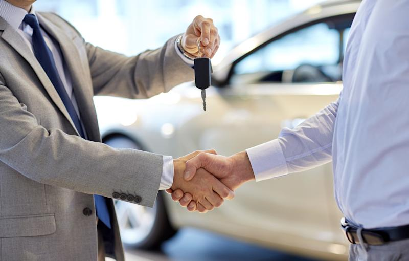 A customer receiving the keys to his new car from a salesman.