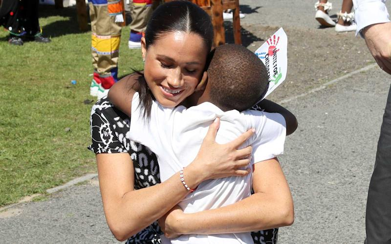 Meghan, Duchess of Sussex receives a hug from a young wellwisher as she visits a Justice Desk initiative in Nyanga township, with Prince Harry, Duke of Sussex, during their royal tour of South Africa on September 23, 2019 in Cape Town, South Africa. The Justice Desk initiative teaches children about their rights and provides self-defence classes and female empowerment training to young girls in the community. | Chris Jackson/Getty Images