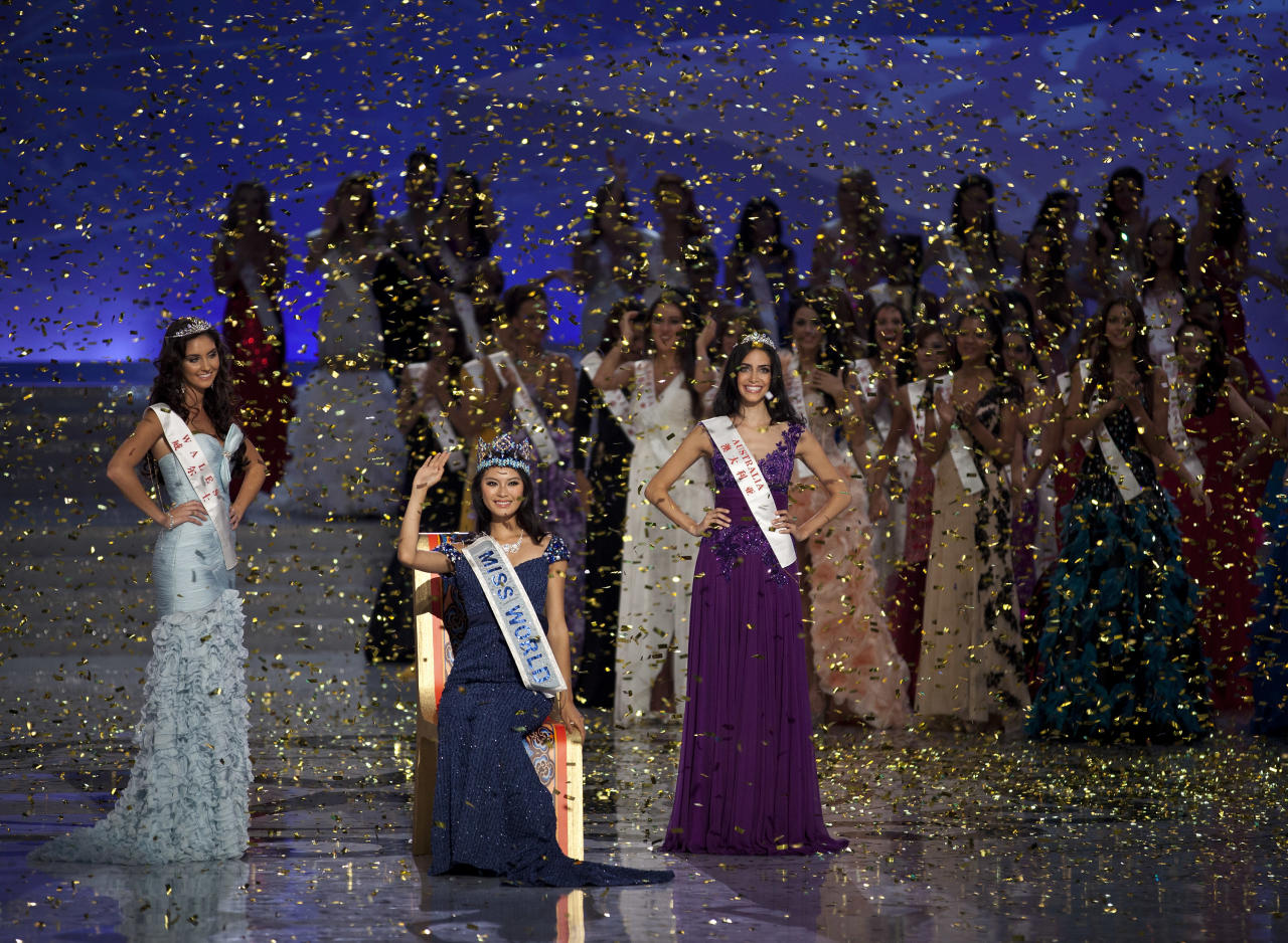 Newly crowned Miss World Yu Wenxia of China, center, waves flanked by first runner-up Miss Wales, Sophie Moulds, left, and 2nd runner-up Miss Australia Jessica Kahawaty, right, during the Miss World 2012 beauty pageant at the Ordos Stadium Arena in inner Mongolia, China Saturday, Aug. 18, 2012. (AP Photo/Andy Wong)