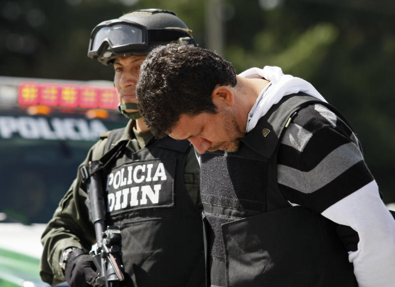Alleged drug trafficker Juan Carlos Calle Serna, right, looks down while escorted by police in handcuffs and body armor after being deported from Ecuador, at a police station in Bogota, Colombia, Sunday March 18, 2012. Calle Serna was captured in Quito, Ecuador on Friday. (AP Photo/Nestor Silva)