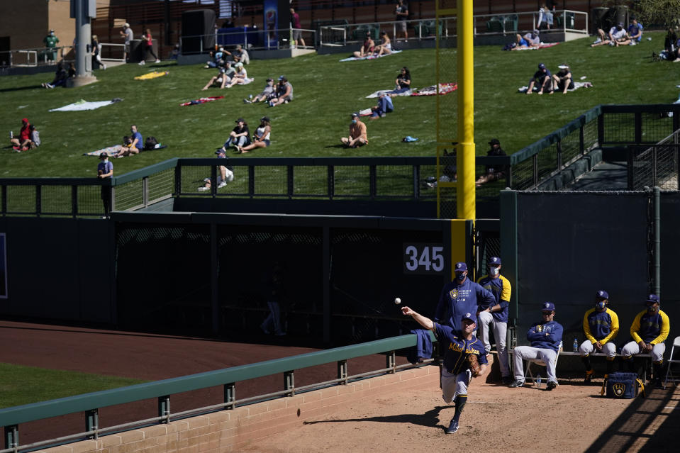 Milwaukee Brewers pitcher Jordan Zimmermann, bottom right, warms up in the bullpen as socially distanced fans watch the Brewers' spring baseball game with the Arizona Diamondbacks in Scottsdale, Ariz., Monday, March 1, 2021. (AP Photo/Jae C. Hong)