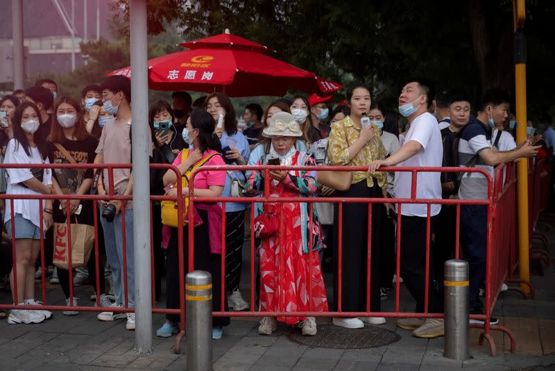 People wait for a rehearsal of a fireworks display near the National Stadium ahead of the 100th founding anniversary of the Communist Party of China in Beijing