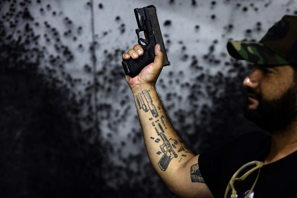 Shooting range owner Wemerson Alkmim poses for a photo showing off his gun tattoos at his Valparaiso Shooting Club on the outskirts of Brasilia, Brazil, Saturday, March 6, 2021. Brazilian President Jair Bolsonaro is pushing to deliver on his promise to arm every person that wants it. His newly-issued gun decrees, which will take effect in April unless congress or courts intervene, worry public security analysts, but excite his base. (AP Photo/Eraldo Peres)