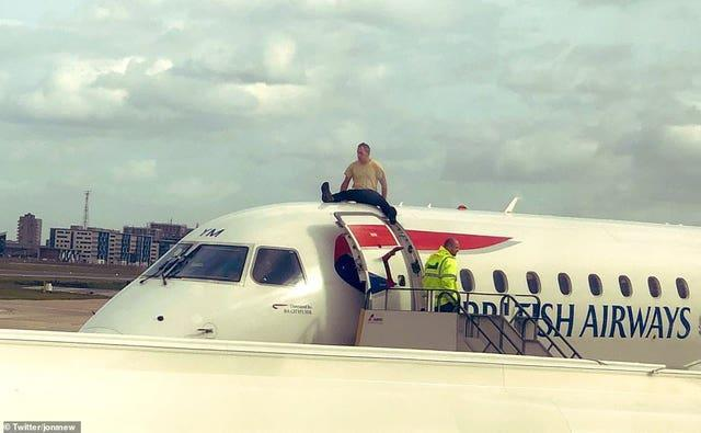 Extinction Rebellion activist James Brown on top of a plane on October 10 2019 during a protest