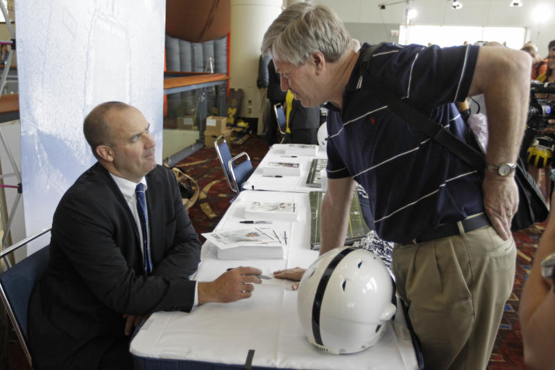 Penn State head football coach Bill O'Brien, left, visits with fans as part of Big Ten Media Days and Kickoff Luncheon, Friday, July 27, 2012, in Chicago. (AP Photo/M. Spencer Green)
