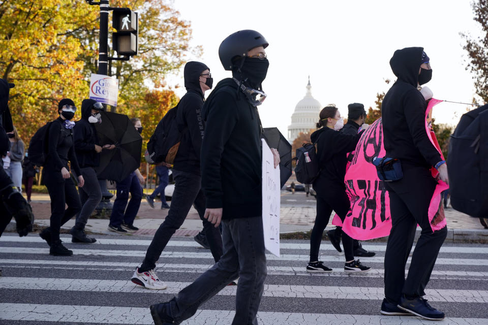 With the U.S. Capitol building in the background, people walk during an anti-Trump march Saturday Nov. 14, 2020, in Washington. (AP Photo/Jacquelyn Martin)
