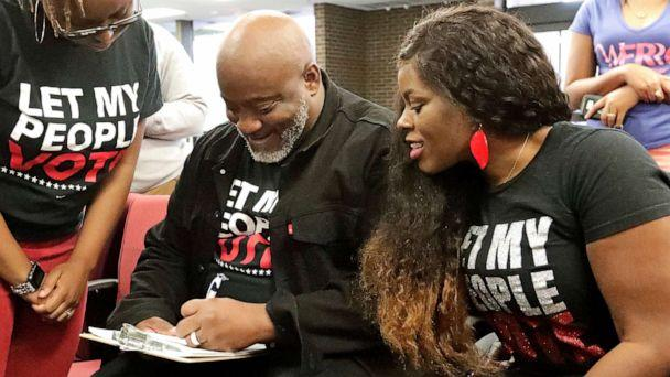 PHOTO: In this Jan. 8, 2019, file photo, former felon Desmond Meade and president of the Florida Rights Restoration Coalition, left, fills out a voter registration form as his wife Sheena looks on at the Supervisor of Elections office in Orlando, Fla. (John Raoux/AP, FILE)