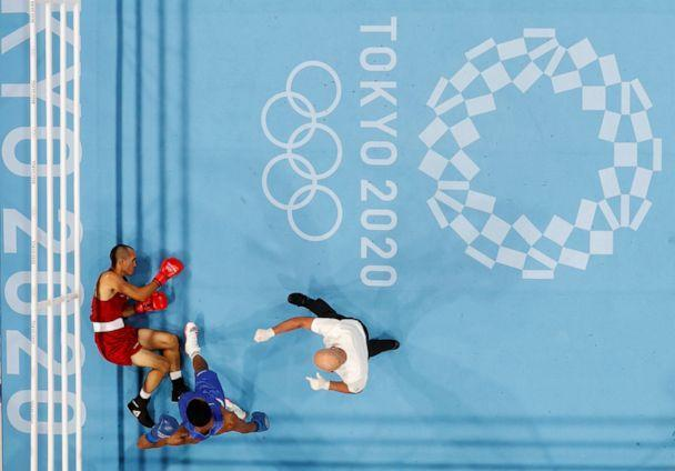 PHOTO: Eldric Sella Rodriguez of the Refugee Olympic Team lies on the ground after being knocked down during his fight against Euri Cedeno Martinez of the Dominican Republic on July, 26, 2021, in Tokyo. (Ueslei Marcelino/Reuters)