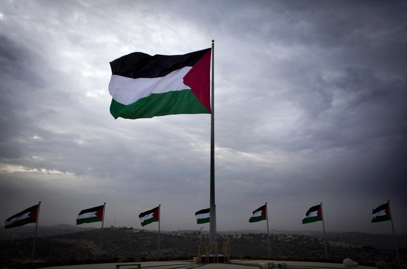 In this photo taken Dec. 3, 2013, a giant Palestinian national flag flutters from the highest point of the city and over looking the neighboring Israeli settlement of Ateret in the background, at the under construction Palestinian city of Rawabi, north of the West Bank city of Ramallah. A state-of-the art Palestinian city under construction in the West Bank, with residential towers, parks, an outdoor mall and a convention center has become a symbol of national pride. (AP Photo/Nasser Nasser)