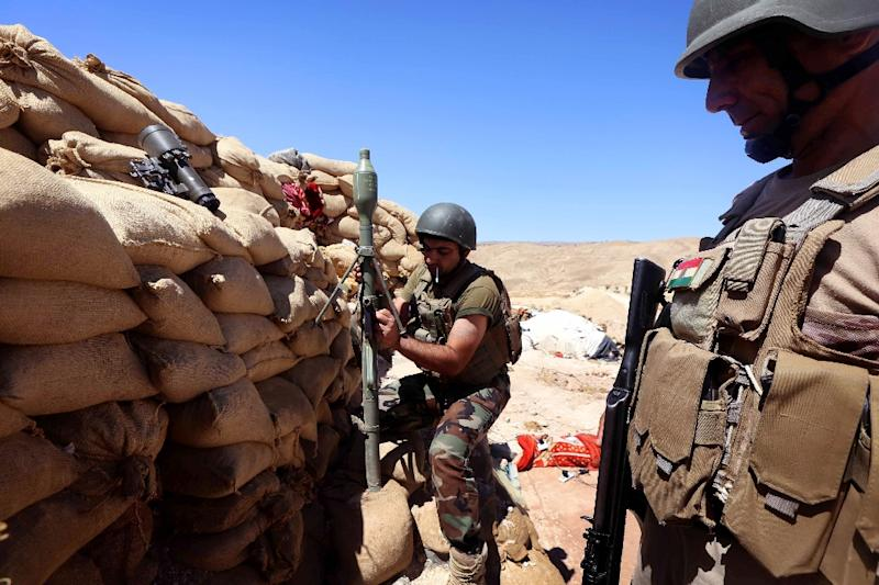 Kurdish Peshmerga fighters prepare a mortar shell on the frontline against Islamic State (IS) group militants near the northern Iraqi town of Sinjar, west of the city of Mosul on August 17, 2015