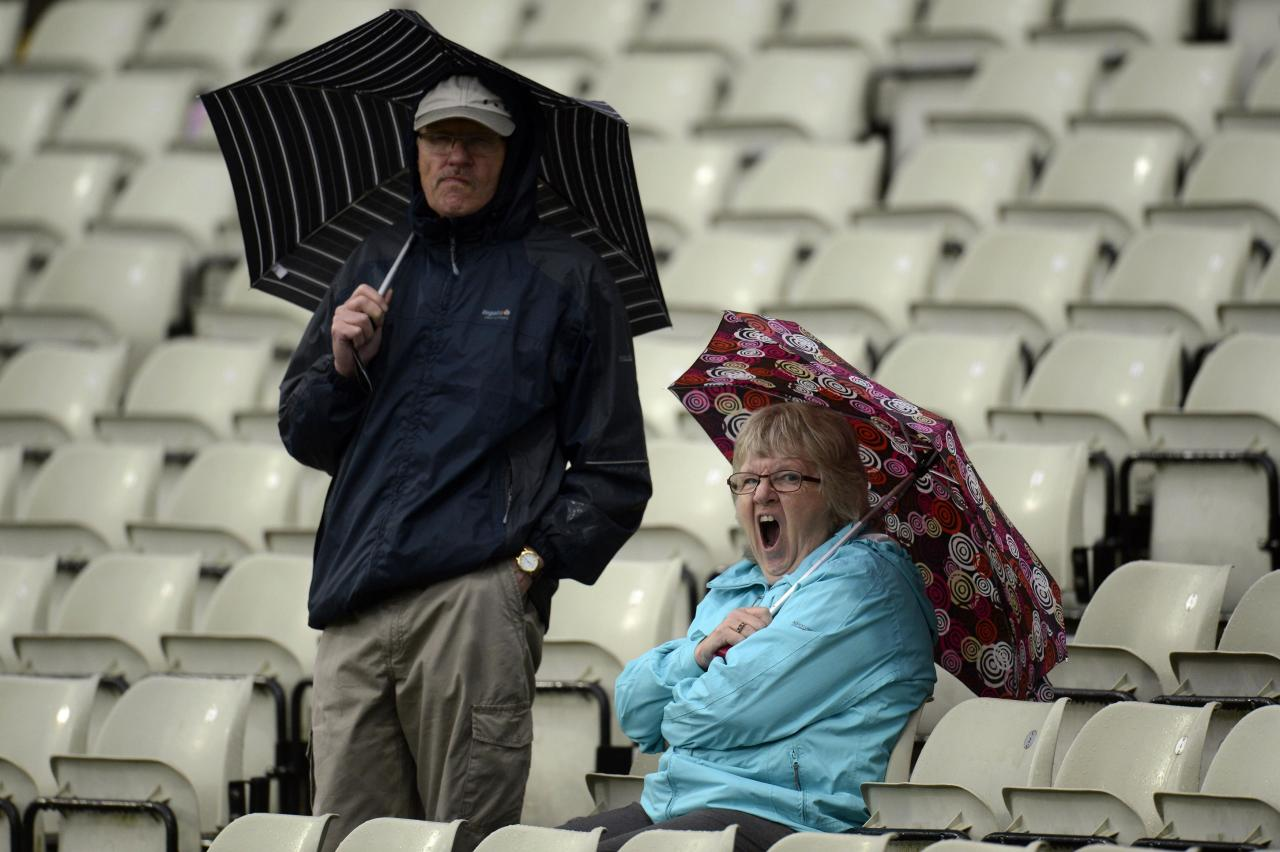 Spectators with umbrellas wait as rain falls during the third one-day international between England and Australia at Edgbaston cricket ground in Birmingham September 11, 2013. REUTERS/Philip Brown (BRITAIN - Tags: SPORT CRICKET)