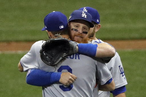 Los Angeles Dodgers' Justin Turner hugs Chris Taylor (3) after Game 2 of the National League Championship Series baseball game against the Milwaukee Brewers Saturday, Oct. 13, 2018, in Milwaukee. The Dodgers won 4-3. (AP)