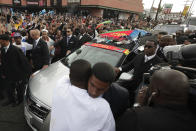 FILE - In this April 11, 2019 file photo, two men embrace as a hearse carrying the casket of slain rapper Nipsey Hussle passes through a dense crowd in Los Angeles. The 25-mile procession traveled through the streets of South Los Angeles after his memorial service, including a trip past Hussle's clothing store, The Marathon, where he was gunned down March 31. A year after Hussle's death, his popularity and influence are as strong as ever. He won two posthumous Grammys in January, he remains a favorite of his hip-hop peers and his death has reshaped his hometown of Los Angeles in some unexpected ways.(AP Photo/Jae C. Hong, File)