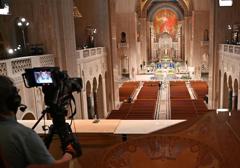 A cameraman films members of the clergy arriving for an online Easter Sunday Mass in front of empty pews at the Basilica of the National Shrine of the Immaculate Conception in Washington, D.C., on April 12. (Photo: EVA HAMBACH via Getty Images)