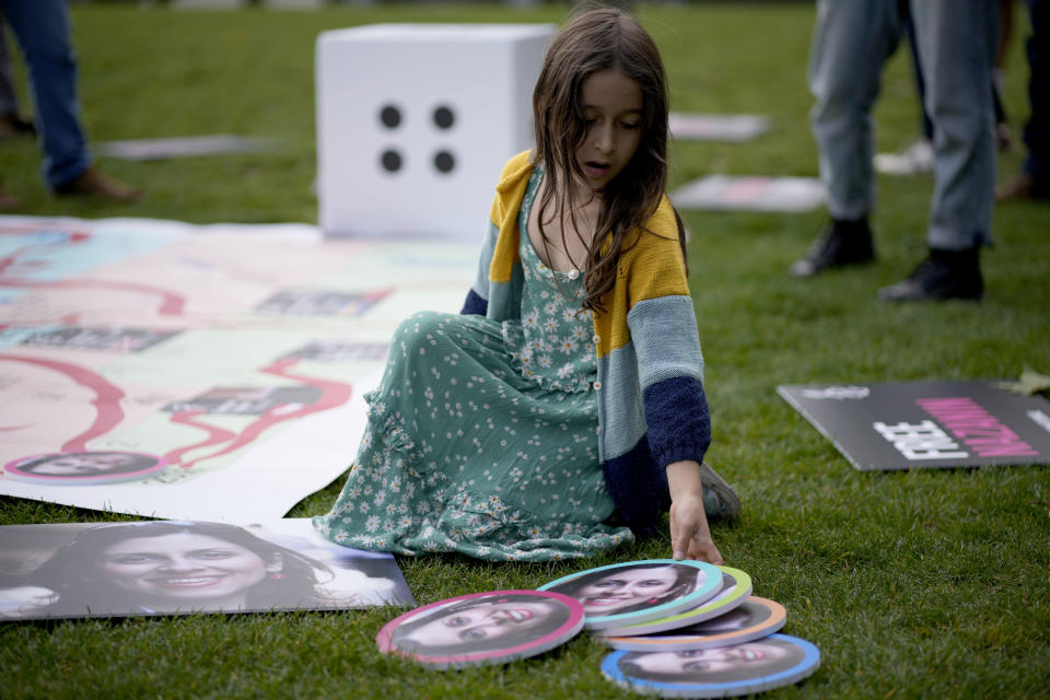 """Gabriella, the seven year old daughter of imprisoned British-Iranian Nazanin Zaghari-Ratcliffe joins in a game with counters with photographs of her mother on a giant snakes and ladders board in Parliament Square, London, to show the """"ups and downs"""" of Zaghari-Ratcliffe's case to mark the 2,000 days she has been detained in Iran, Thursday, Sept. 23, 2021. Zaghari-Ratcliffe was originally sentenced to five years in prison after being convicted of plotting the overthrow of Iran's government, a charge that she, her supporters and rights groups deny. While employed at the Thomson Reuters Foundation, the charitable arm of the news agency, she was taken into custody at the Tehran airport in April 2016 as she was returning home to Britain after visiting family. (AP Photo/Matt Dunham)"""