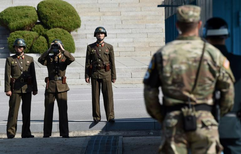 North Korean soldiers (L) look at the South side at the truce village of Panmunjom in the Demilitarized Zone