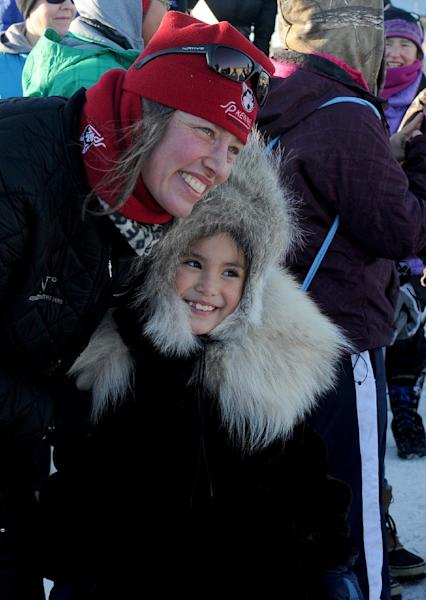 Aliy Zirkle poses for the photo with 8-year-old Autumn Nanouk. Zirkle is the first musher to reach the Bering Sea in Unalakleet during the 2014 Iditarod Trail Sled Dog Race on Saturday, March 8, 2014. Autumn's grandmother, Rhoda Nanouk, made Nanouk's wolf ruff parka. (AP Photo/The Anchorage Daily News, Bob Hallinen)