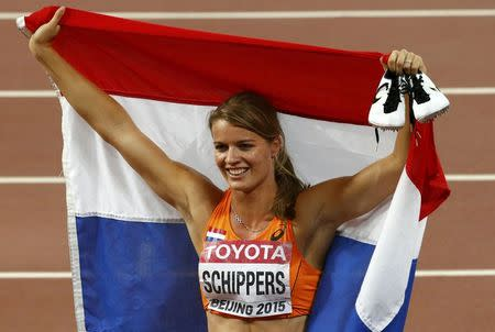 Dafne Schippers of the Netherland holds her national flag as she celebrates after winning the women's 200m final during the 15th IAAF World Championships at the National Stadium in Beijing, China, August 28, 2015. REUTERS/David Gray