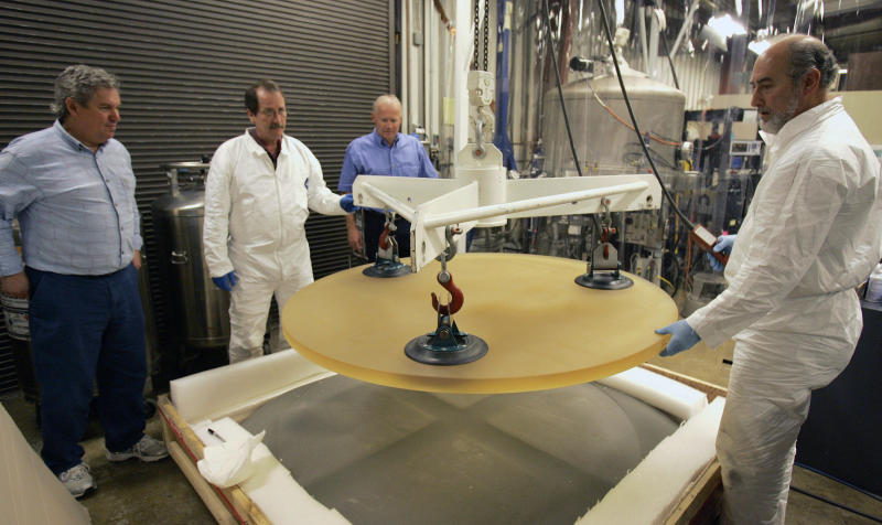 FILE - In this Jan. 7, 2008, file photo, Thirty Meter Telescope Project Scientist Jerry Nelson, left, and Telescope Optics Group Leader Eric Williams, third from left, inspect a 500 pound glass blank as it is removed from packing by Dave Hilyard, Chief Optician at University of California, right, and Brian Dupraw at the UC Observatory Optical Lab at the University of California at Santa Cruz, Calif. Hawaii officials are demobilizing law enforcement at a mountain where protesters are blocking construction of a giant telescope because the project isn't moving forward for now. An international consortium wants to build the Thirty Meter Telescope on Mauna Kea, Hawaii's tallest peak. But some Native Hawaiians believe the telescope will desecrate sacred land. Protesters have stopped construction from going forward since mid-July. (AP Photo/Ben Margot, File)