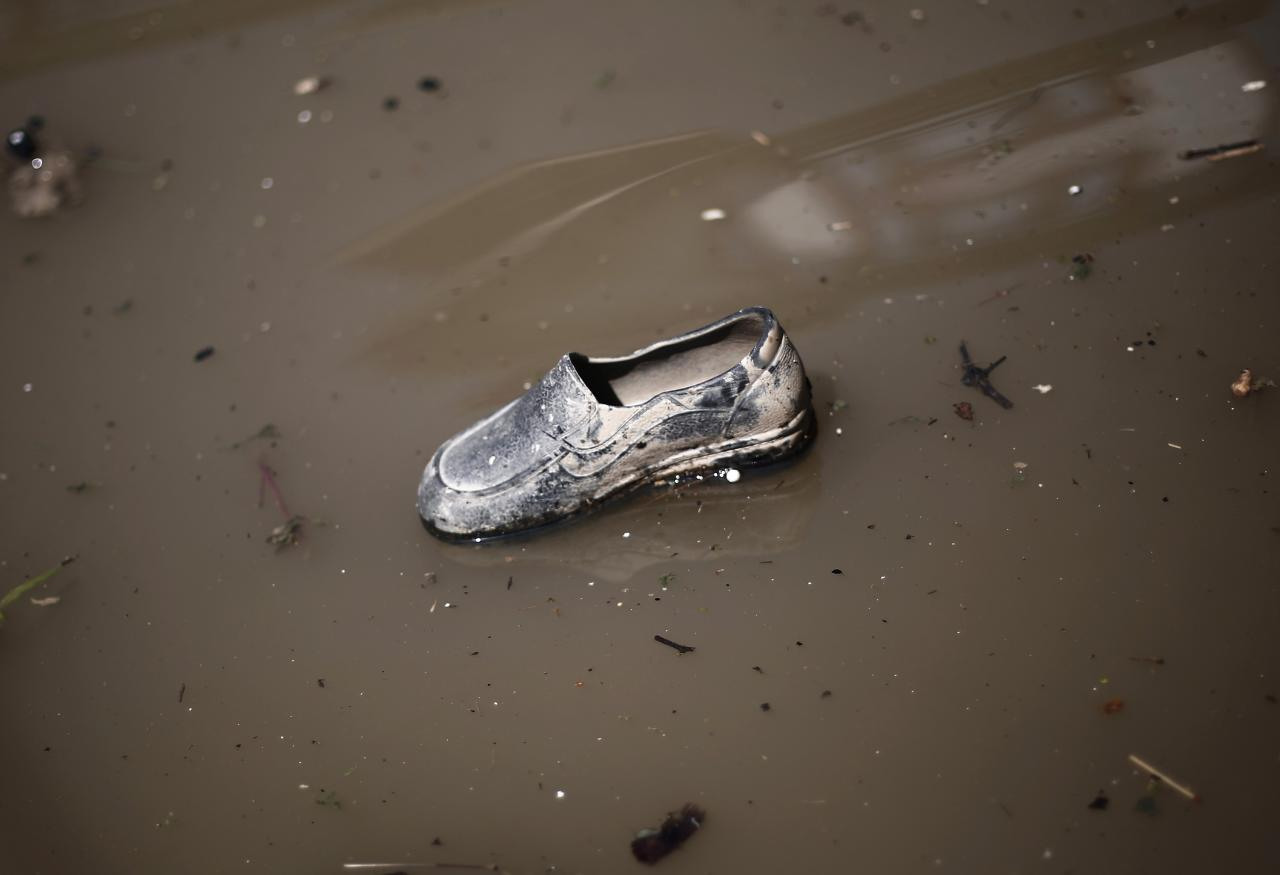 A shoe floats in floodwaters along a street in Srinagar September 15, 2014. Indian emergency workers battled on Monday to prevent waterborne diseases from spreading, as fetid water swilled around the Kashmir valley more than a week after the region's worst flooding in more than a century. REUTERS/Adnan Abidi (INDIAN-ADMINISTERED KASHMIR - Tags: DISASTER ENVIRONMENT)