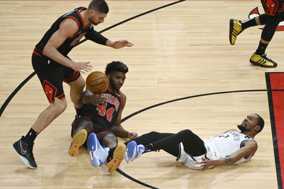 Brooklyn Nets forward Kevin Durant (7) chases the ball away from Chicago Bulls forward Patrick Williams (44) and center Nikola Vucevic, left, during the second half of an NBA basketball game Tuesday, May 11, 2021, in Chicago. (AP Photo/Matt Marton)