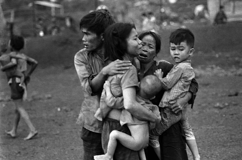 FILE - In this June 1965 file photo shot by Associated Press photographer Horst Faas, South Vietnamese civilians, among the few survivors of two days of heavy fighting, huddle together in the aftermath of an attack by government troops to retake the post at Dong Xoai, Vietnam. Faas, a prize-winning combat photographer who carved out new standards for covering war with a camera and became one of the world's legendary photojournalists in nearly half a century with The Associated Press, died Thursday May 10, 2012. He was 79. (AP Photo/Horst Faas)
